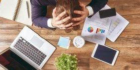 Verzweifelter Mann am Schriebtisch mit Laptop und Smartphone