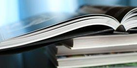 Aufgeschlagenes Buch liegt auf einem Stapel