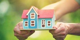 Hände halten Miniatur-Holzhaus