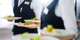 Kellner in der Gastronomie mit mehreren Tellern