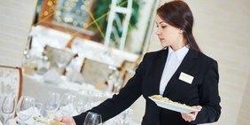 Kellnerin in der Gastronomie deckt Tisch ein