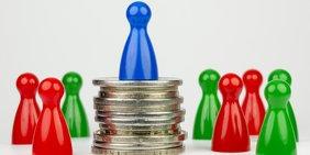 Spielfiguren stehen um eine blaue Spielfigur, die erhöht auf einem Münzstapel steht