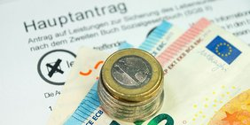 Münzen und Geldscheine auf einem Hartz-IV Antrag