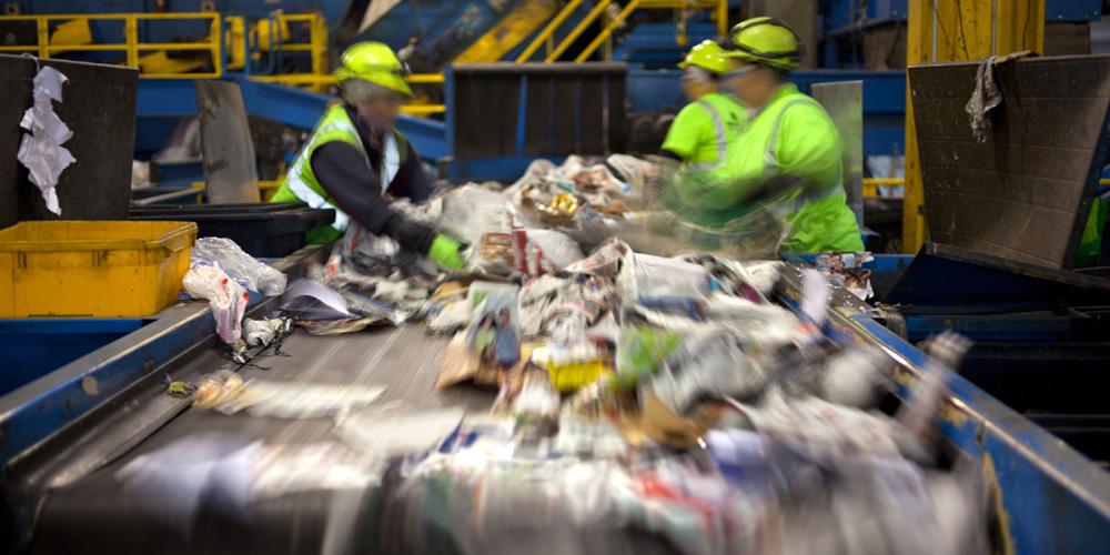 Beschäftigte am Fließband bei Müllsortierung