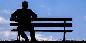 Silhouette von einem alten Mann der auf einer Parkbank sitzt