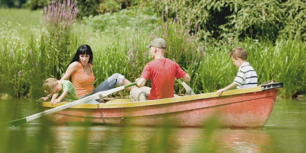 Familie mit zwei Kindern in Ruderboot auf einem kleinen See (sommerlich)
