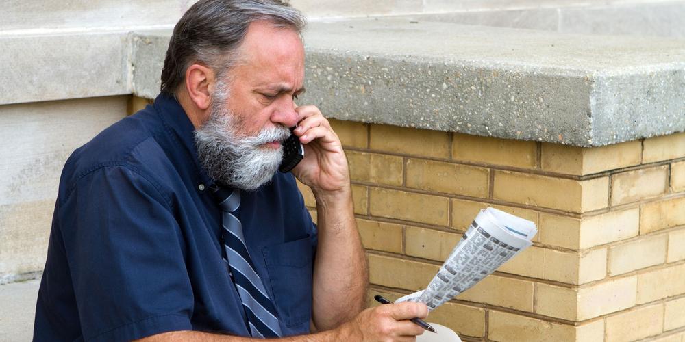 Älterer Mann mit Zeitung telefoniert