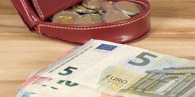 Rote Geldbörse mit Münzen und Geldscheine