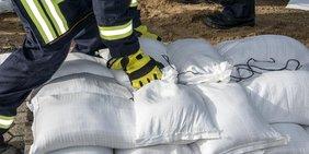 Feuerwehrmann stapelt Sandsäcke