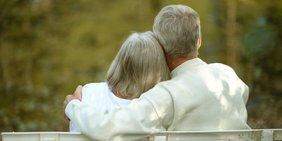 Älteres Paar sitzt Arm in Arm auf einer Parkbank
