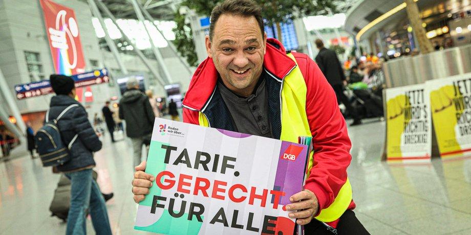 """Thomas Ziegler mit Schild """"Tarif. Gerecht. Für alle."""" am Düsseldorfer Flughafen 8.10.2019"""