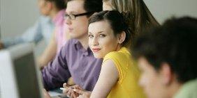 junge Frau sitzt in einer Reihe von Kollegen/innen vor Bildschirmen