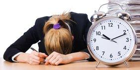 Frau liegt mit Kopf (schlafend) auf Schreibtisch; daneben eine übergroßer Wecker