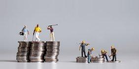 Zwei Münzstapel mit Miniaturfiguren: Auf einem hohen Stapel spielen Menschen Golf, auf einem kleinen Stapel arbeiten Menschen in gebückter Haltung auf dem Bau