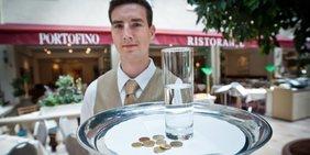 Kellner mit wenig Geld auf dem Teller