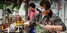 Junger Mann schweißt in einer Werkstatt